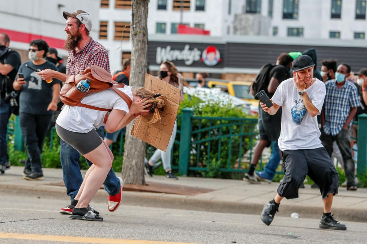 People react after the explosion of a flash bomb fired by police in Minneapolis, Minnesota, on May 27, 2020.