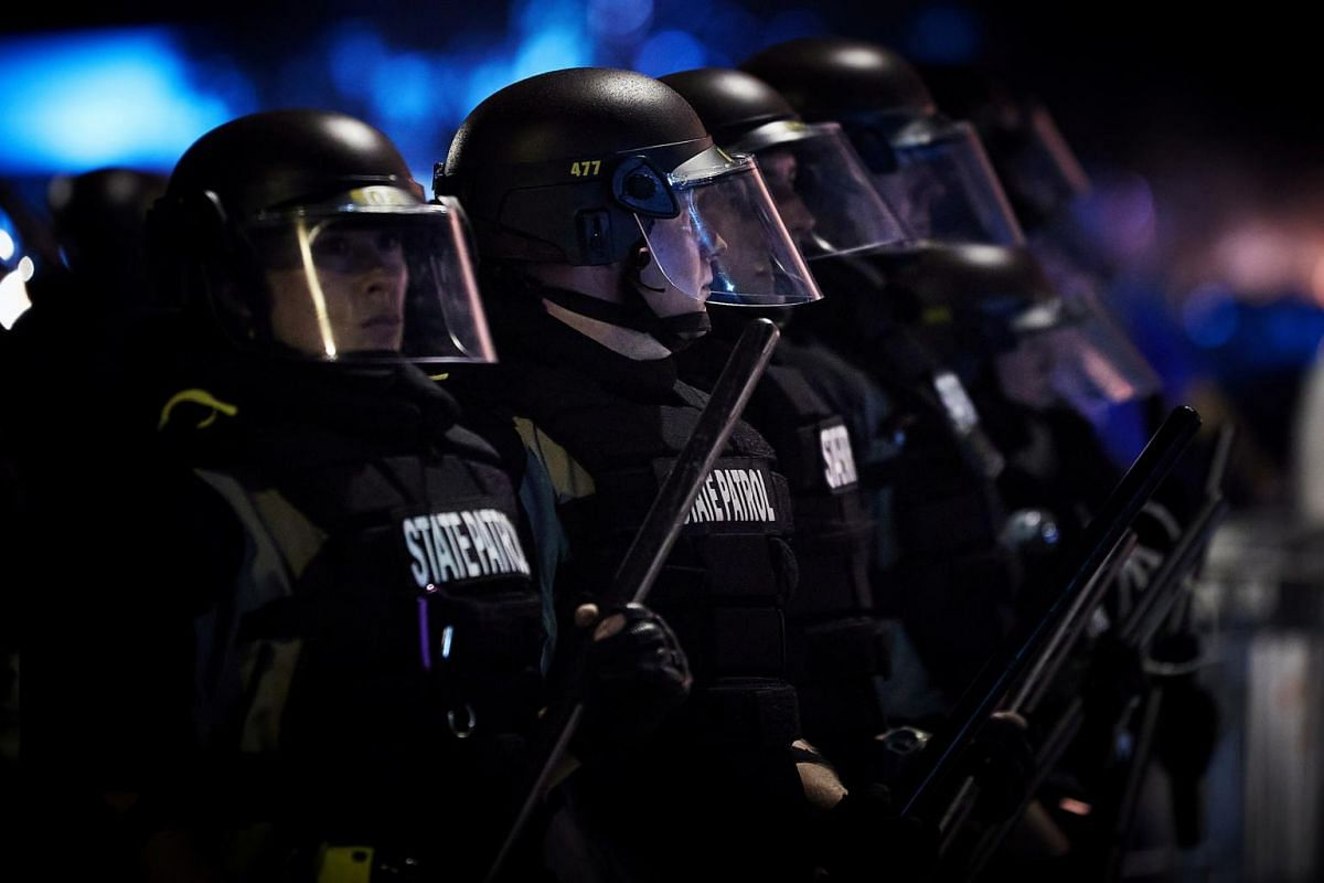 Police officers stand in line in riot gear near the Minneapolis Police Third precinct on May 28, 2020.