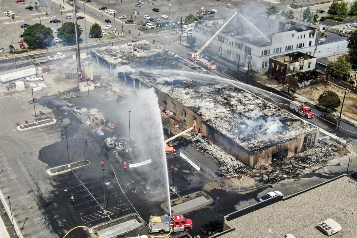 Firefighters battling fires set near the Minneapolis police Third Precinct in Minneapolis, Minnesota on May 28, 2020.