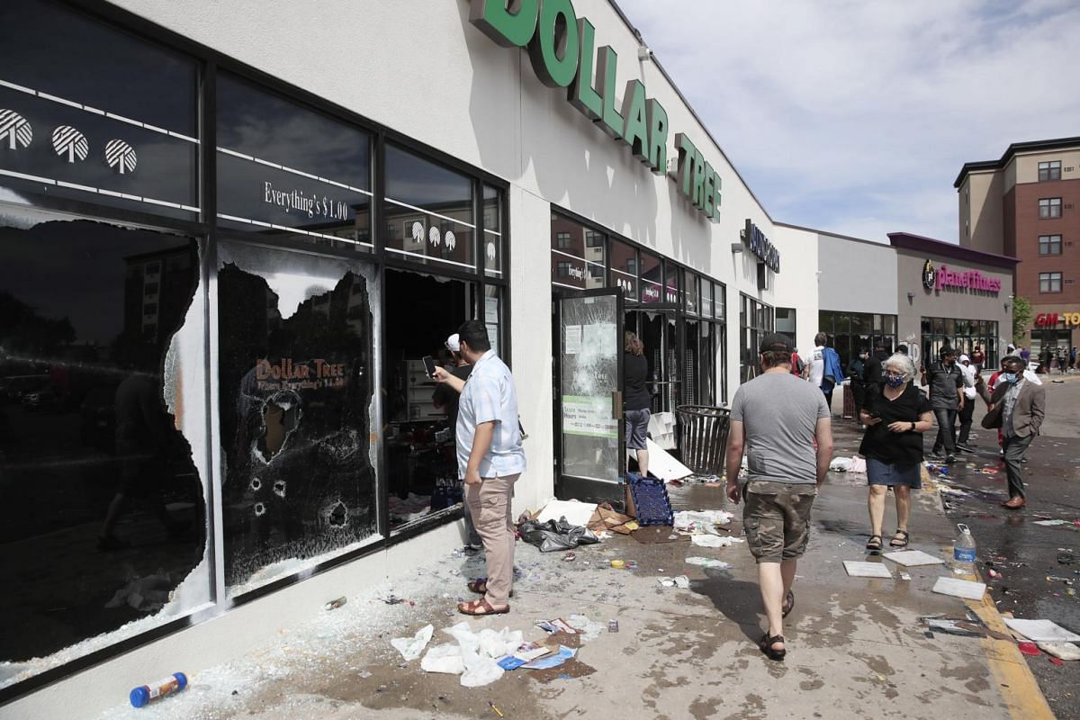 People walk past a destroyed and grafitti-covered Dollar Tree store after a night of rioting and vandalism in Minneapolis, Minnesota on May 28, 2020.