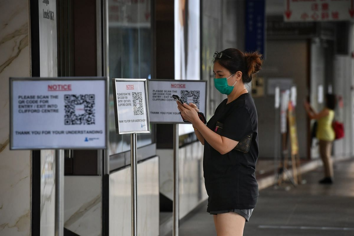 A woman uses the SafeEntry check-in system before entering The Arcade on June 2, 2020.