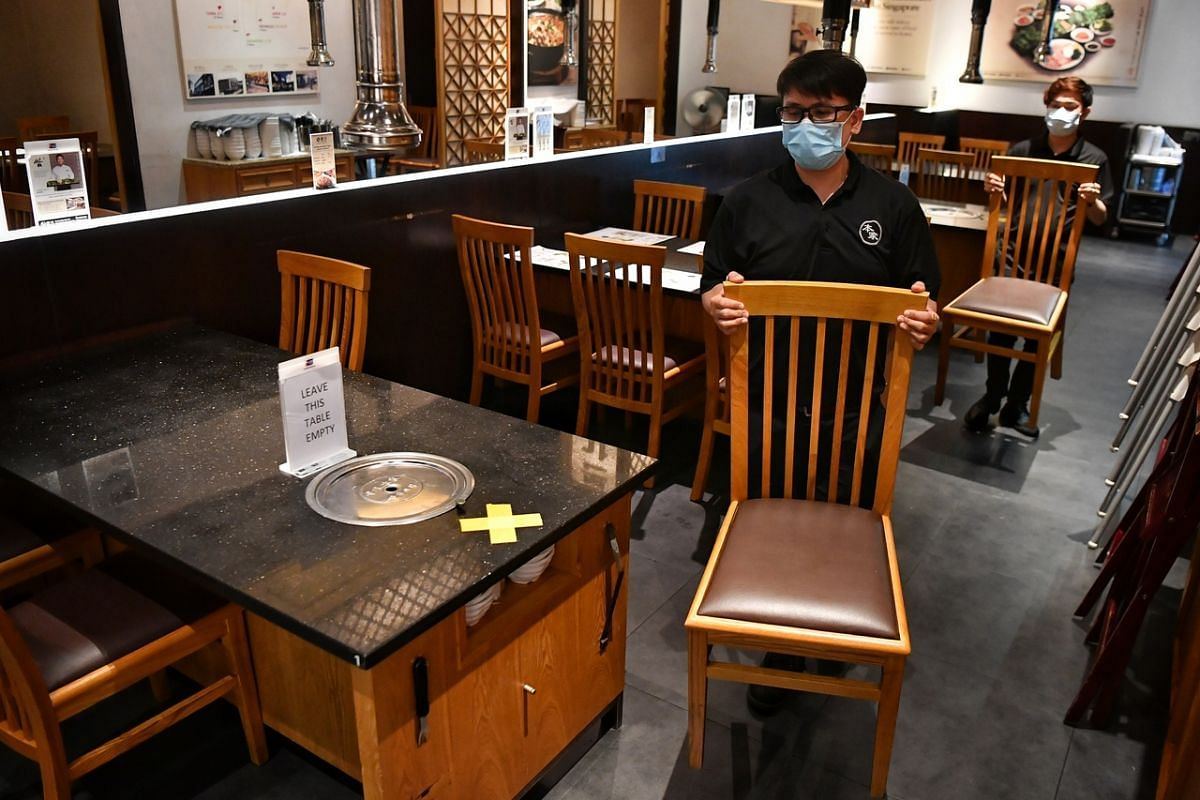 Staff at Korean restaurant Bornga in Suntec City arranging tables and chairs according to phase two safety measures on June 18, 2020.