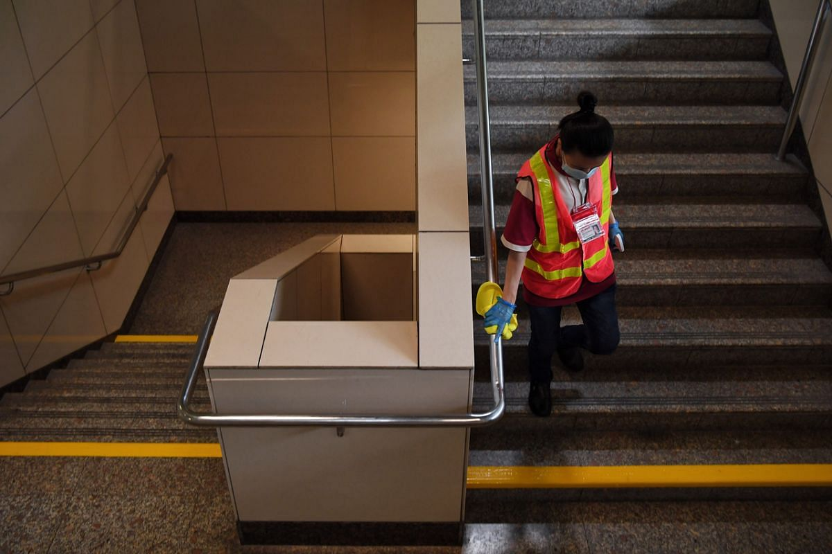 A worker cleaning the handrails of a flight of stairs at Ang Mo Kio MRT station on June 17, 2020.