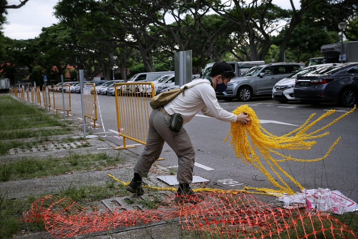 National Parks Board staff removing a cordon at the East Coast Park Food Centre carpark on June 18, 2020.