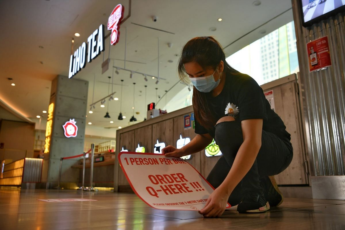 An employee pasting safe distancing stickers at the LiHo outlet in Suntec City on June 18, 2020.
