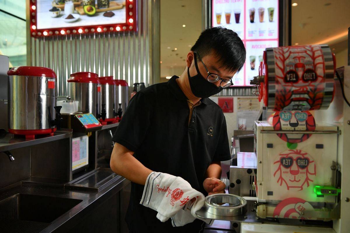 An employee cleaning a machine at the LiHo outlet in Suntec City on June 18, 2020.