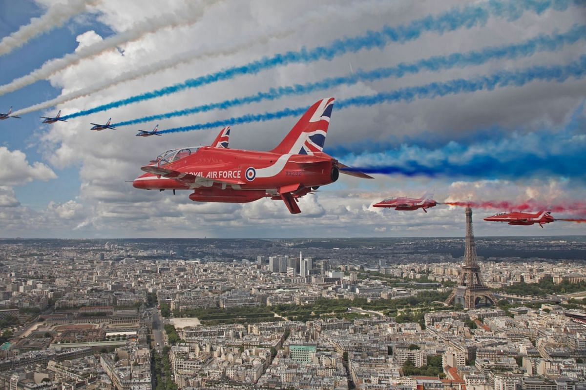 In a handout picture released by the British Ministry of Defence (MOD) on June 18, 2020, The Royal Air Force Aerobatic Team, the Red Arrows, and the French Air Force Aerobatic Team, La Patrouille de France, perform a fly-past over Paris, France, to m