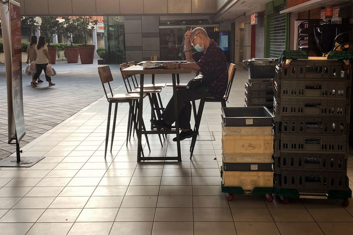 An elderly man reads the papers at the Toa Payoh bus interchange, on June 19, 2020.