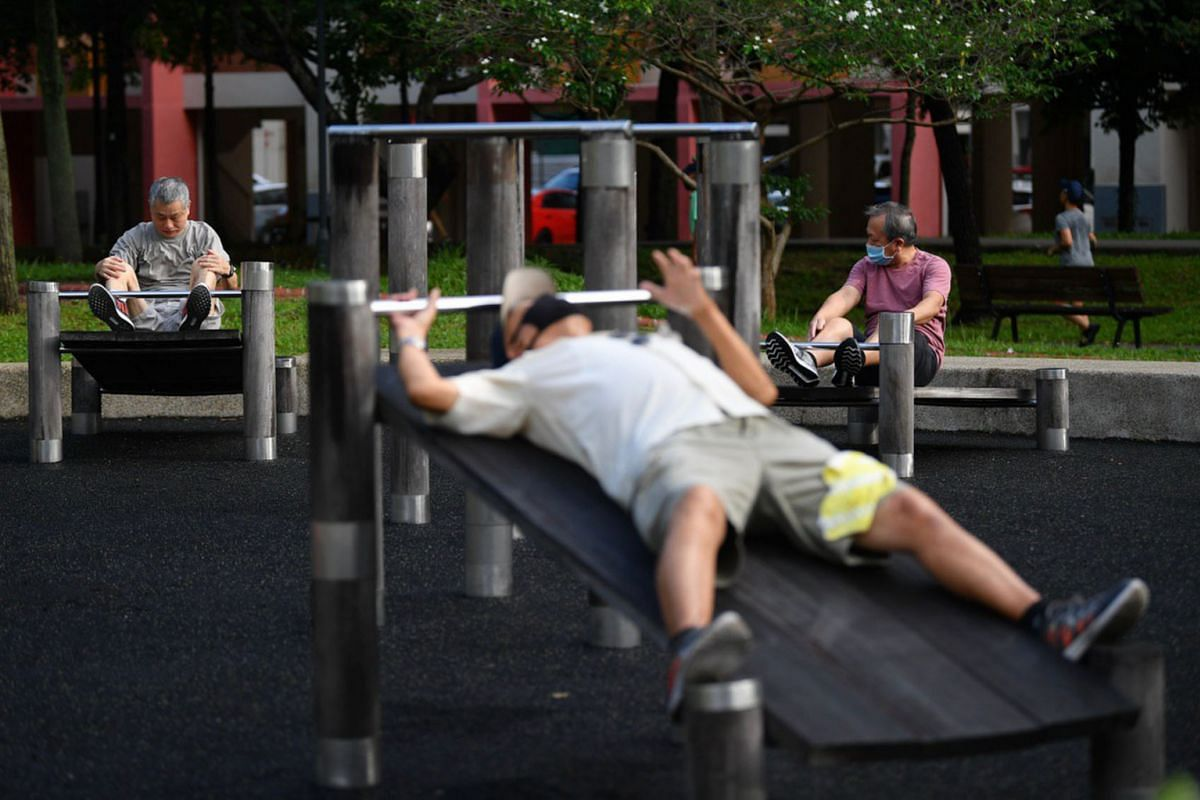 Men exercise at the fitness corner at Tampines Central Park, on June 19, 2020.