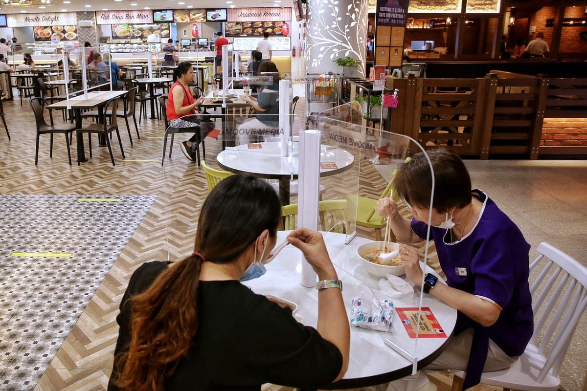 Diners at Thomson Plaza's Koufu foodcourt on June 19, 2020. Table shields have been installed at the foodcourt as part of a month-long trial.