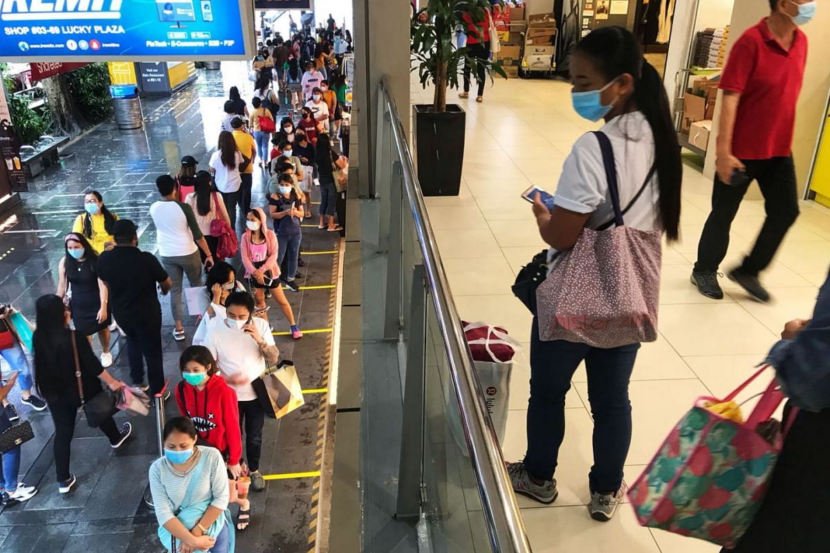 People waiting in line to enter Lucky Plaza on June 21, 2020. The queue moved quickly as people scanned their identity cards or the SafeEntry QR code and had their temperatures taken. Once inside, most shoppers were seen maintaining a safe distance f