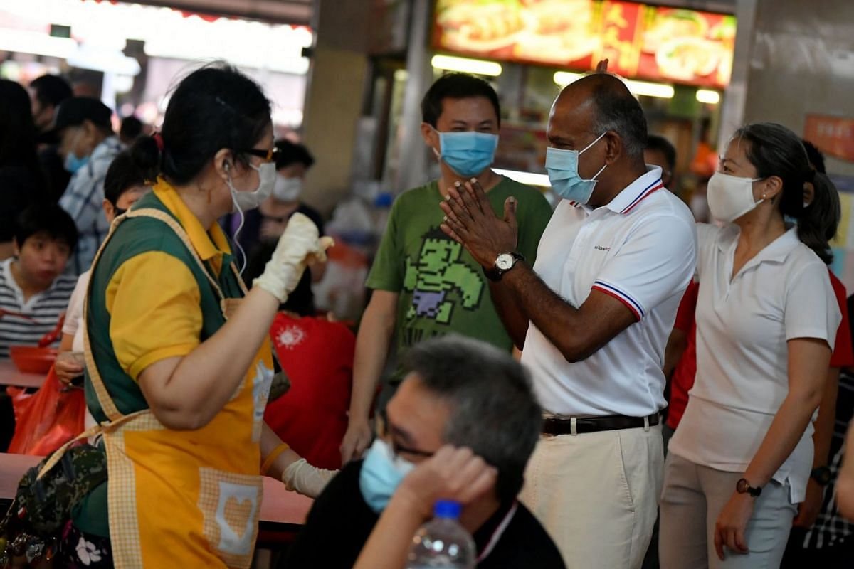 Nee Soon GRC MP and Home Affairs and Law Minister K. Shanmugam and Ms Carrie Tan, (extreme right) 37, founding executive director of Daughters of Tomorrow, interacting with residents at Chong Pang Market & Food Centre on June 21, 2020. PHOTO: THE STR