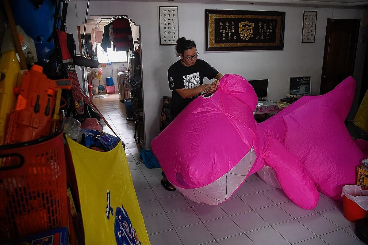 Mr Tan using a cardboard cut-out to trace a part of the coronavirus kite's design onto fabric from an old umbrella. He mostly uses recycled materials or discarded kites to bring his designs to life. Some of Mr Tan's creations during the circuit break