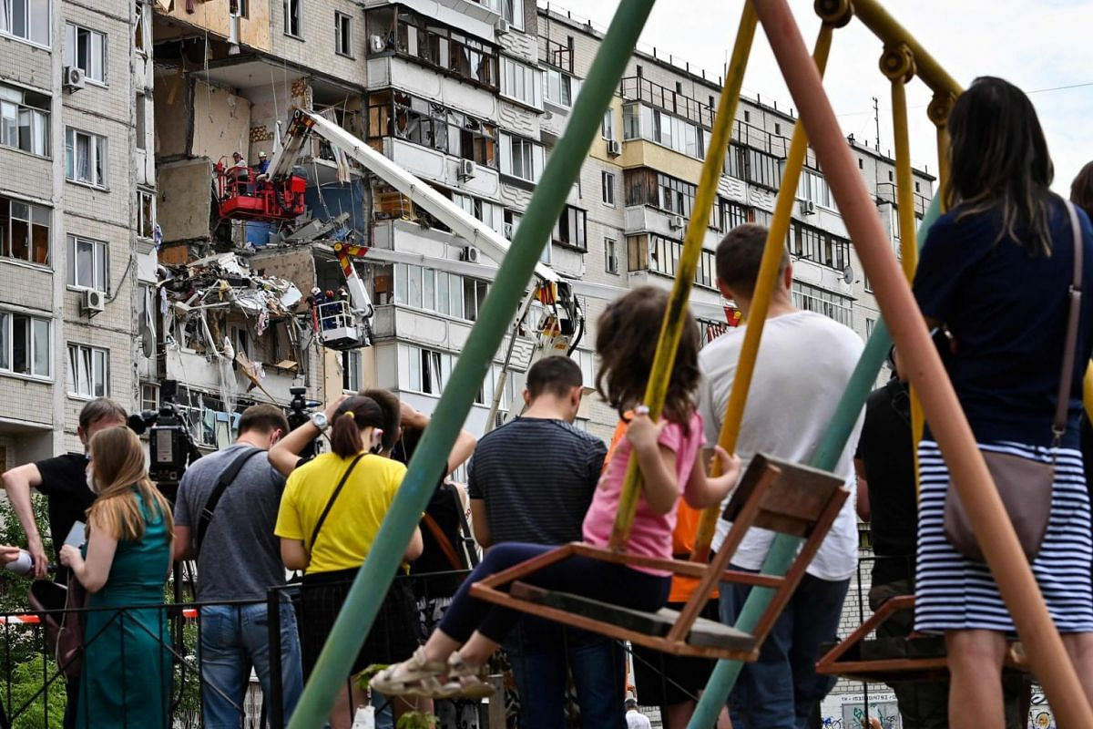 Local residents watch rescuers removing rubbles from the site of a suspected gas explosion that killed one person and ruined several flats in an apartment building, in a residential area of Kiev, on June 21, 2020. PHOTO:  AFP