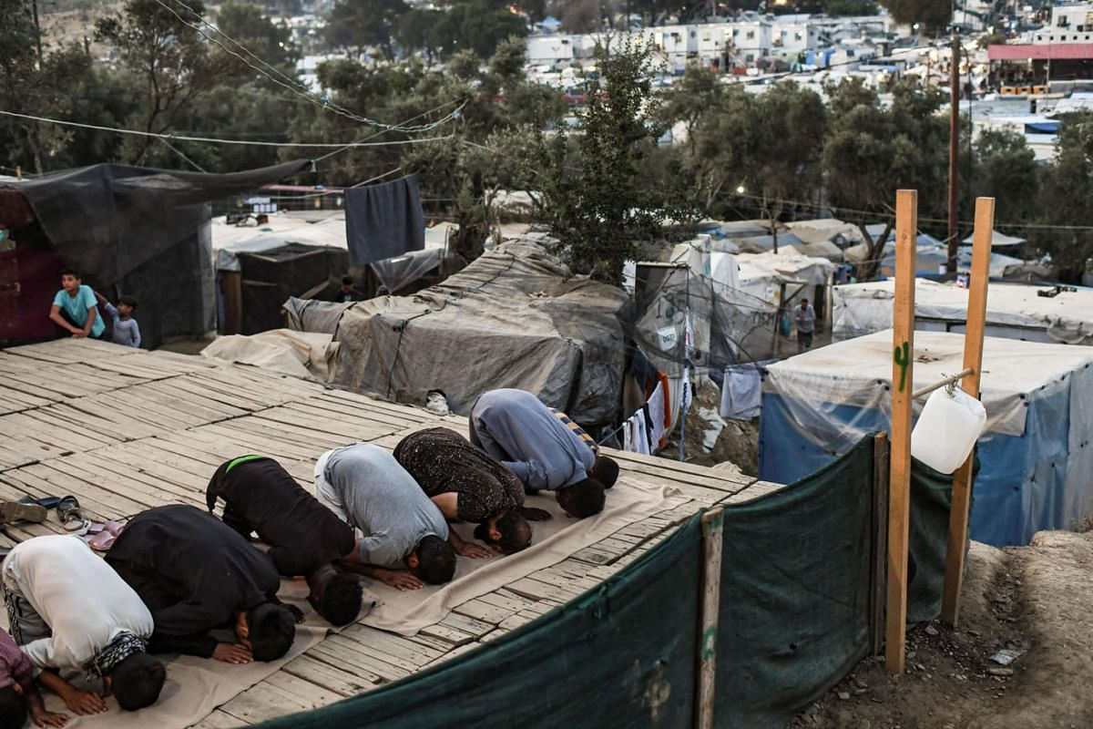 Refugees and migrants pray in a improvised tents camp near the refugee camp of Moria in the island of Lesbos on June 21, 2020. PHOTO: AFP