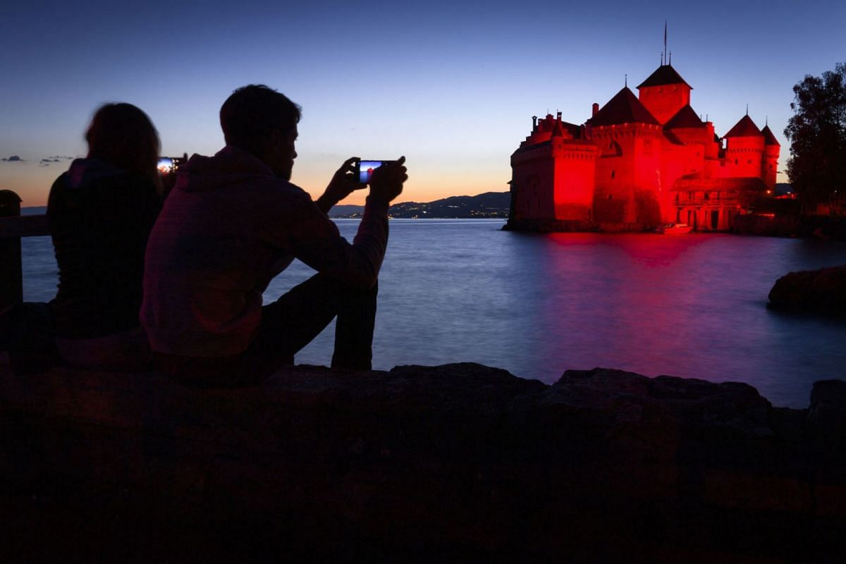The Chillon Castle is lit up in red on the shore of Lake Geneva during the'Night of Light campaign, in Veytaux near Montreux, Switzerland, June 22, 2020. PHOTO: EPA-EFE