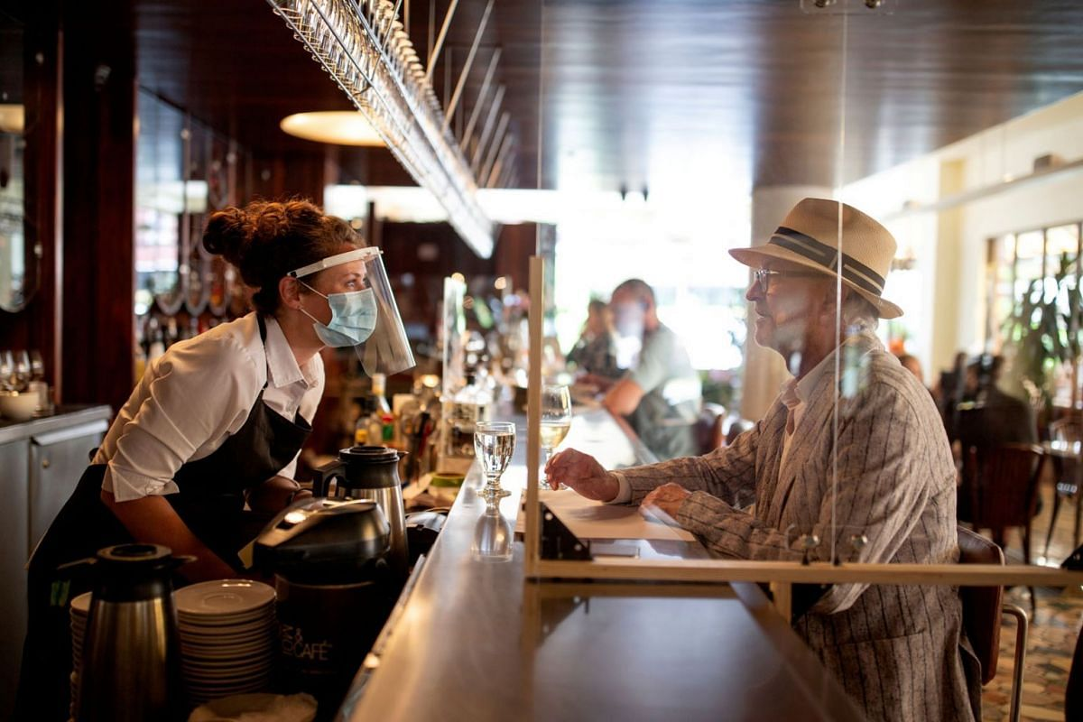 A bartender talks to a patron at Lemeac restaurant on the first day after novel coronavirus restrictions were lifted to visit restaurants in Montreal, Quebec, Canada June 22, 2020. PHOTO: REUTERS
