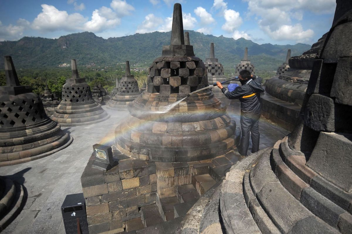 A worker cleans volcanic ash off the stupas at the Borobudur temple in Magelang Regency on June 22, 2020, a day after Mount Merapi erupted in nearby Sleman, sending a plume of ash into the sky. PHOTO:  AFP