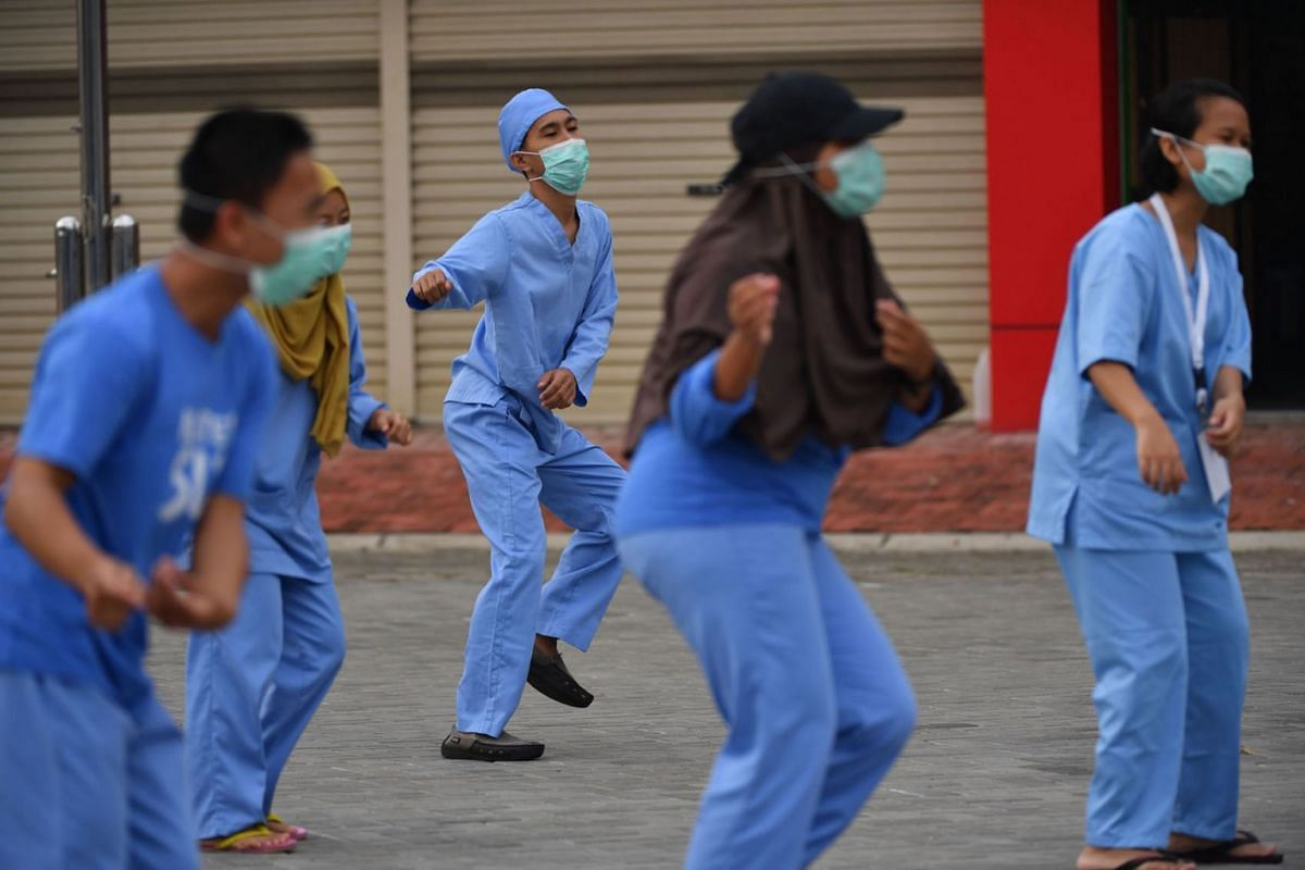 This picture taken on June 22, 2020 shows Indonesian doctors, nurses and volunteers taking part in a group workout in the courtyard of a quarantine facility for coronavirus patients in Tangerang. PHOTO: AFP