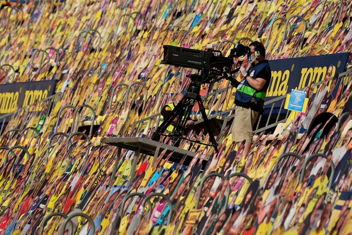 A cameraman works among cardboards of fans prior to the Spanish league football match Villarreal CF against Sevilla FC at La Ceramica stadium in Vila-real on June 22, 2020. PHOTO: AFP