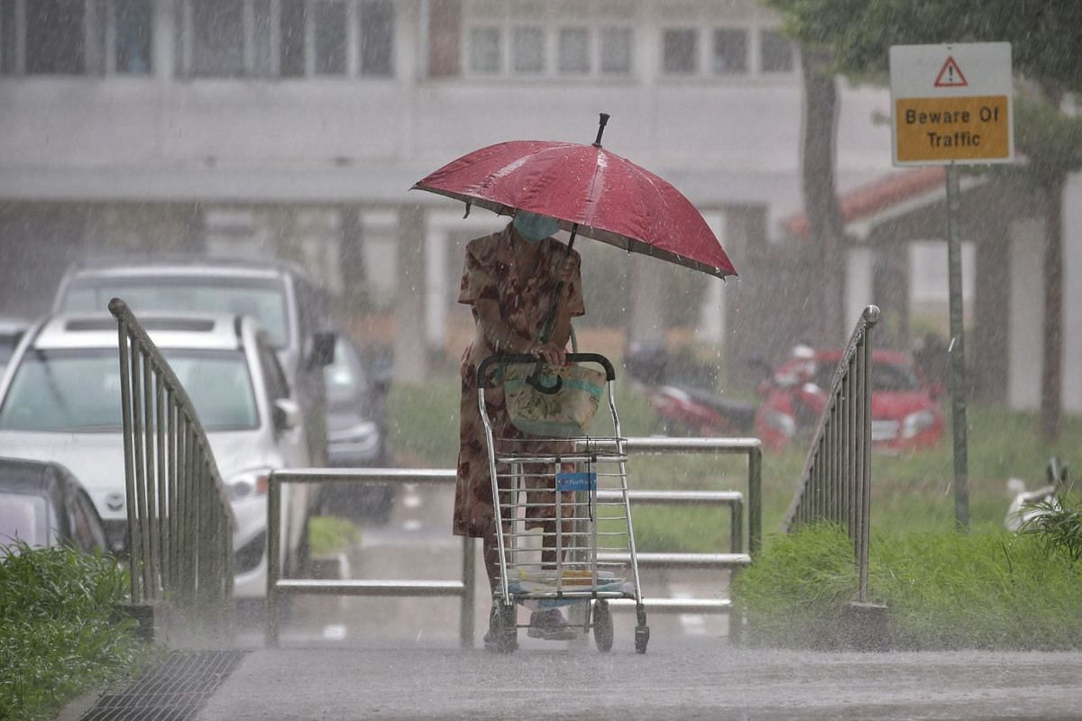 Singapore continued to experience heavy rainfall yesterday, June 24, 2020, including in Bedok South where this elderly woman is seen walking. PHOTO: THE STRAITS TIMES/KEVIN LIM