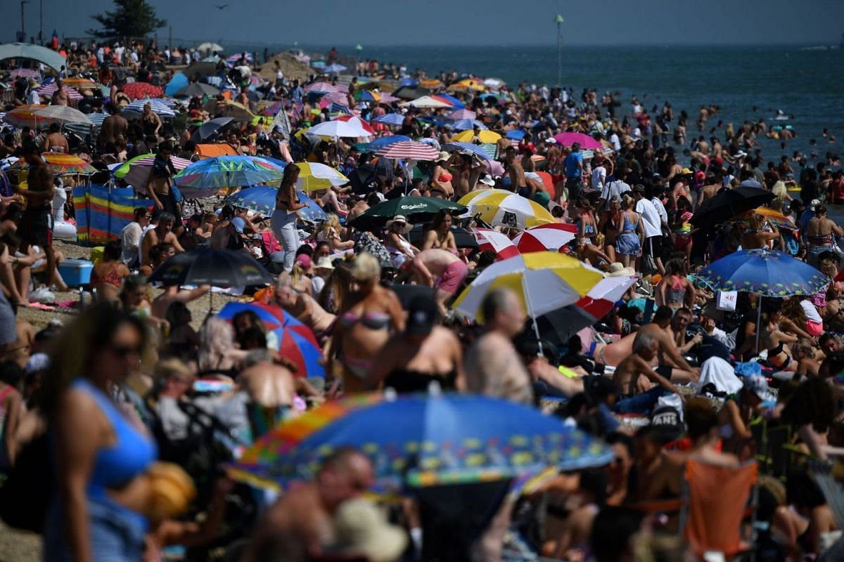 Beachgoers enjoy the sunshine as they sunbathe on the beach and play in the sea in Southend-on-Sea, south east England, on June 24, 2020.  Britain is bracing for a flood of visitors to its beaches as a heatwave hits the continent with temperatures to