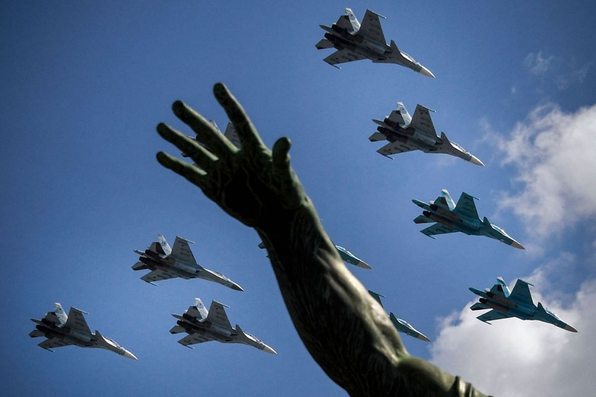 Russian Sukhoi Su-35S fighter aircrafts, Su-34 military fighter jets and Su-30SM jet fighters fly over Red Square during a military parade, which marks the 75th anniversary of the Soviet victory over Nazi Germany in World War Two, in Moscow on June 2