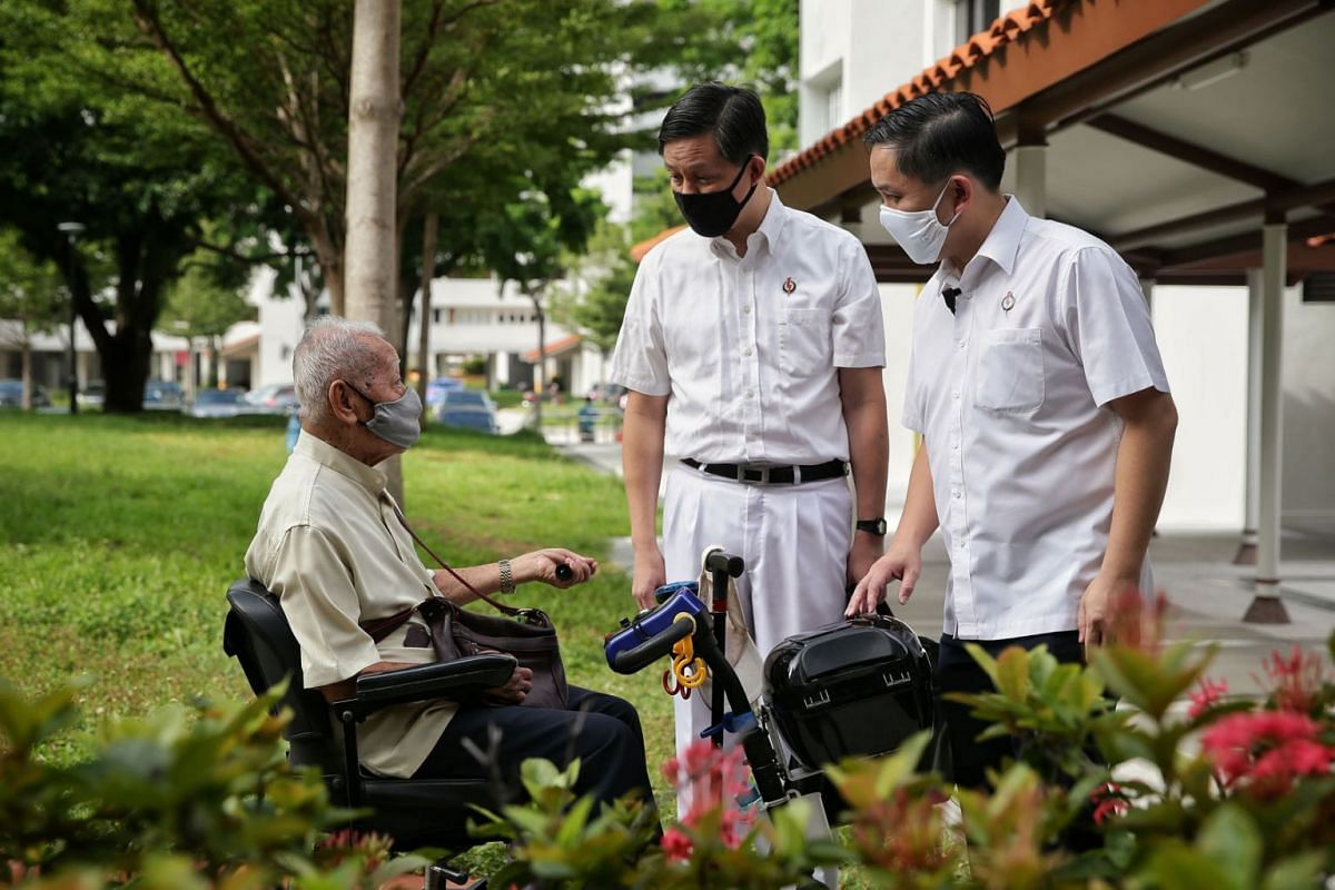 PAP second assistant secretary-general Chan Chun Sing (centre), accompanied by People's Action Party (PAP) headquarters executive director Alex Yam (right), speaking with an elderly resident during his arrival at the party headquarters for the intr