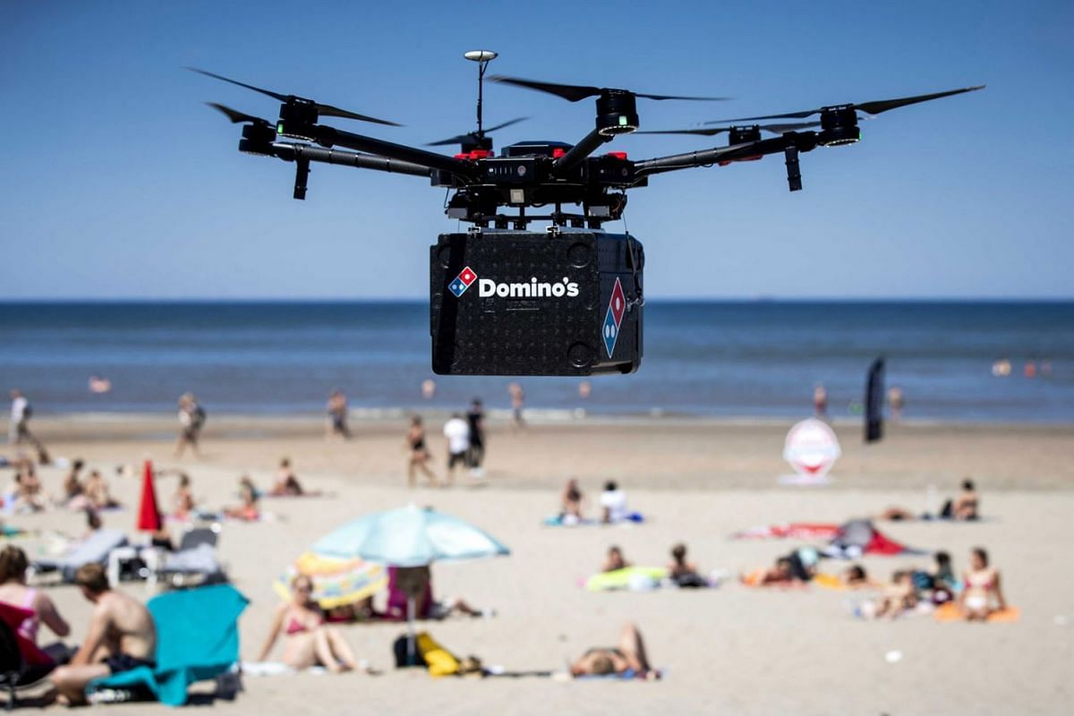 A drone with a box underneath for transporting pizzas during a test run on the beach of Zandvoort, The Netherlands, June 25, 2020. Pizza chain Domino's wants to deliver pizzas with drones. PHOTO: EPA-EFE