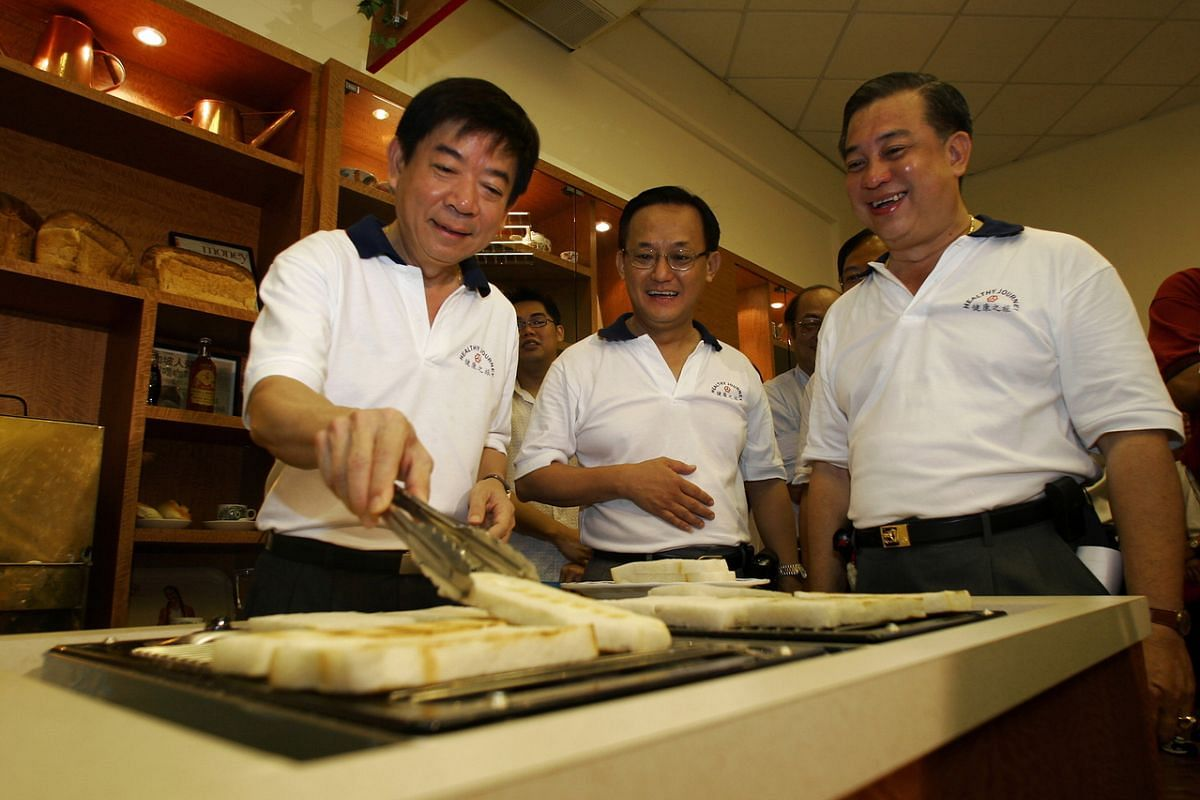 The then Minister for Health Khaw Boon Wan (left) toasting bread at the Ang Mo Kio Community Centre during his visit in 2005.