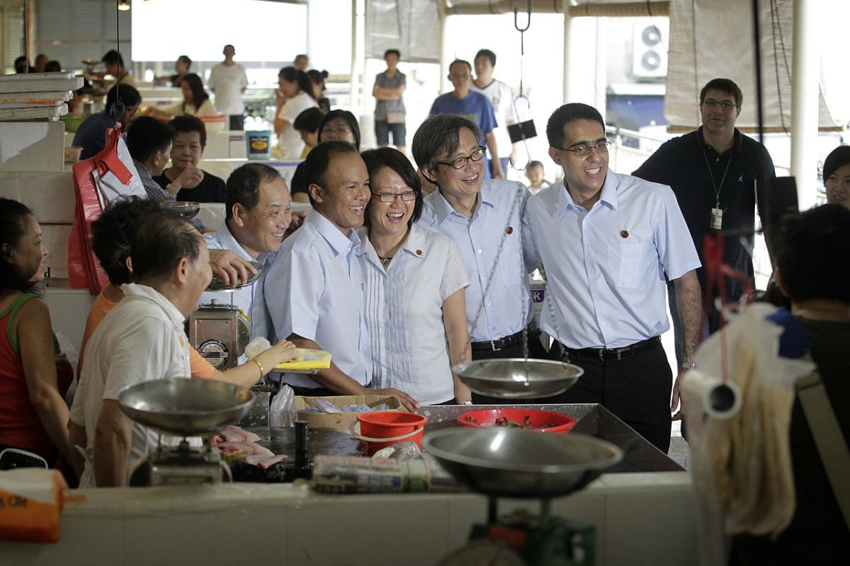 The Workers' Party Aljunied GRC team of (from left) Mr Low Thia Khiang,  Mr Faisal Manap, Ms Sylvia Lim, Mr Chen Show Mao and Mr Pritam Singh taking a picture with stallholders during a walkabout at Kovan Hougang Food Centre on April 30, 2011.