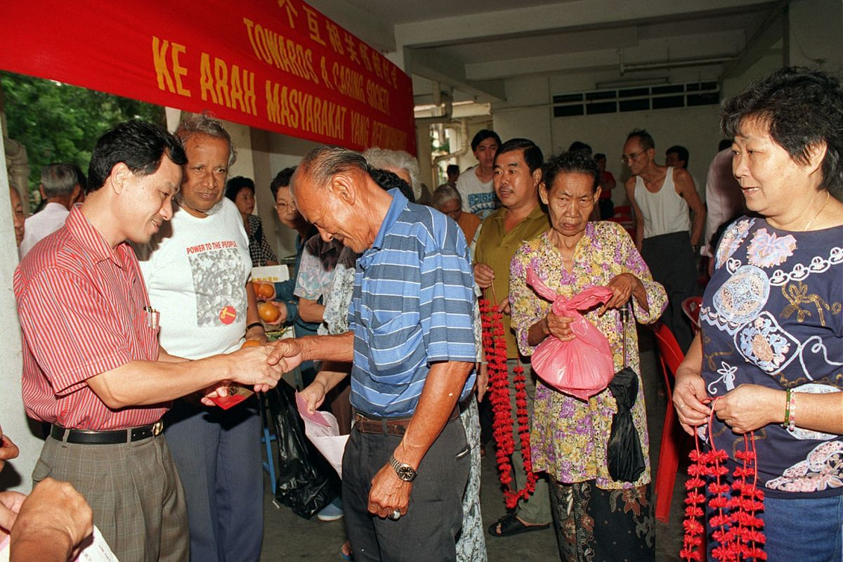 Mr Low (left) and party secretary-general J.B. Jeyaretnam (next to him) distributing hongbao and food hampers to elderly residents in Hougang in 1996.