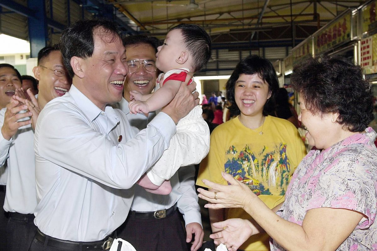 Mr Low carries an eight-month-old Rayson Tan Zhen Yu while meeting Hougang residents during a walkabout with Dr Poh Lee Guan (centre) in 2001.
