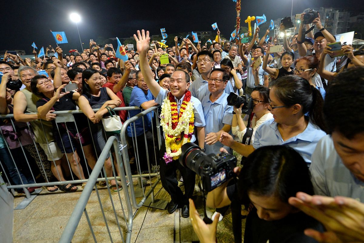 Mr Low (with garlands) waving to supporters at the WP rally for Aljunied GRC at Serangoon Stadium on Sept 8, 2015.