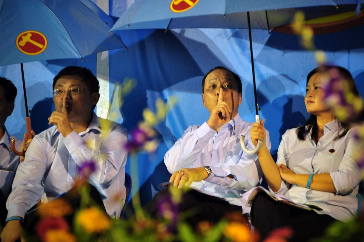 Mr Low (centre) and then Sengkang West candidate Koh Choong Yong (left) seeking silence after supporters started calling for Mr Low to speak during a rally held in Sengkang on May 3, 2011.