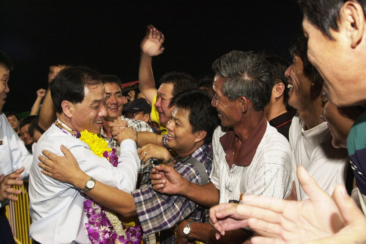 Mr Low surrounded by his supporters as he leaves the Workers' Party election rally at Hougang Stadium on Oct 27, 2001.