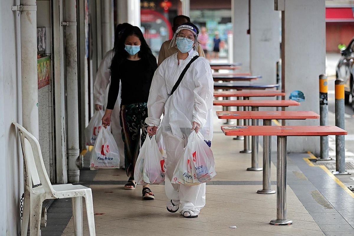 Polytechnic student Lee Ci En, 18, in personal protective gear, helping seniors and families with young children to get groceries from FairPrice supermarket. Hairstylist Sabrina Yue, 41, trimming one of the residents' hair at the stairwell of Block 5