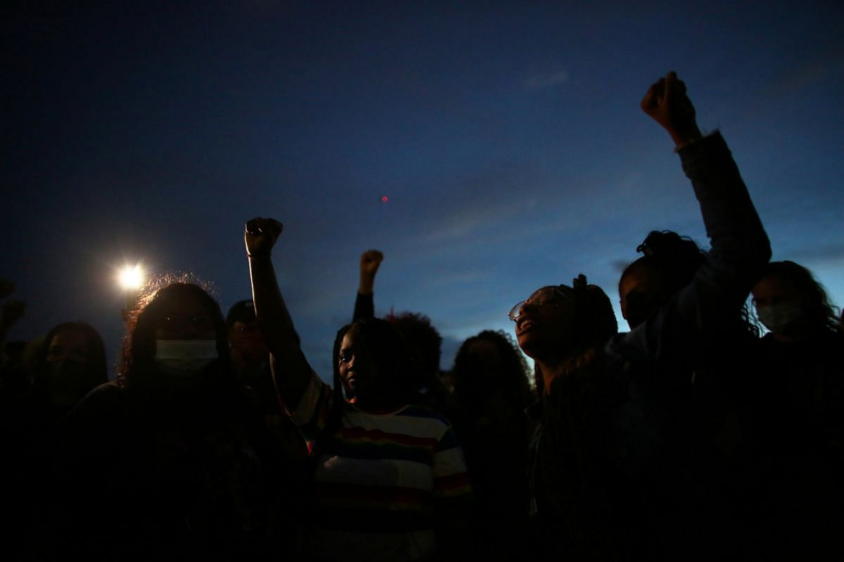 Protesters raise their hands and shout Elijah McClain's name, as a drone flies in the distance, during a demonstration against the killing of McClain and police injustice in Aurora, Colorado, on June 27, 2020.
