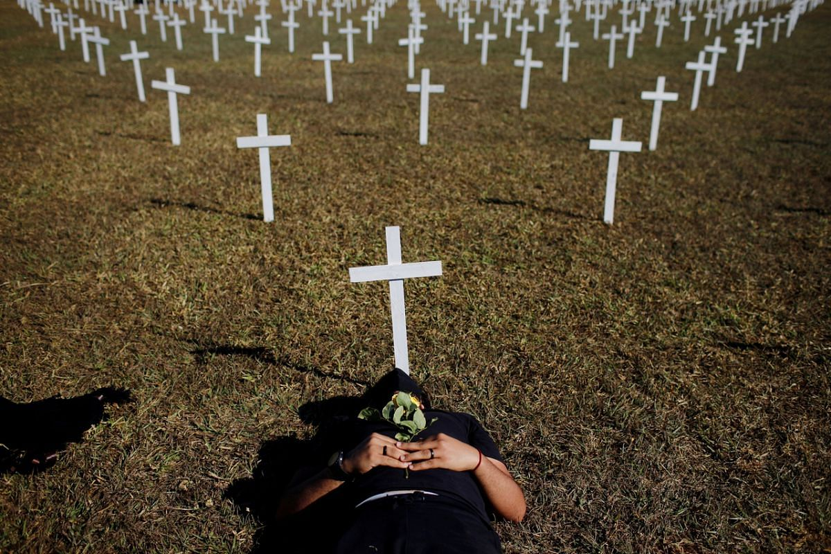 An activist lies next to crosses symbolising people who died from the coronavirus during a protest against Brazil's President Jair Bolsonaro in front of the National Congress in Brasilia on June 28, 2020.