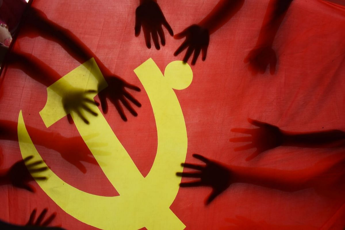 School children place their hands on the Communist Party flag during a class about the history of the Communist Party at a school in Lianyungang, in China's eastern Jiangsu province, on June 28, 2020.