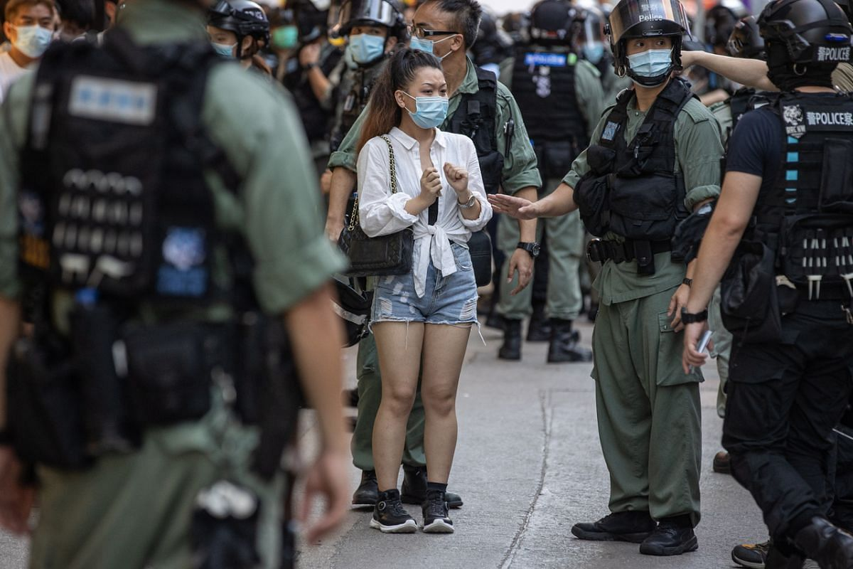 A woman is detained by police during a silent march against the national security law in Hong Kong on June 28, 2020.
