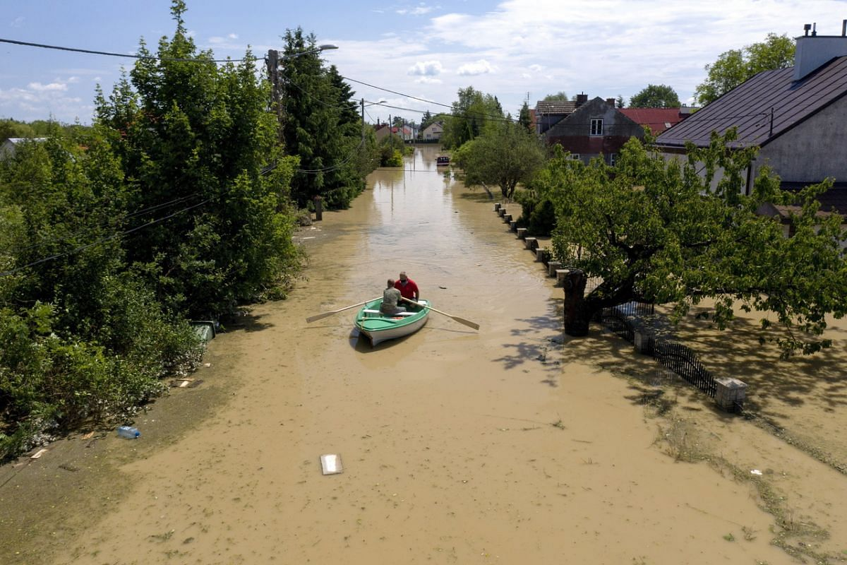 Two men on a rowboat navigate through the flooded streets in the town of Jaslo, southeastern Poland, on June 28, 2020.