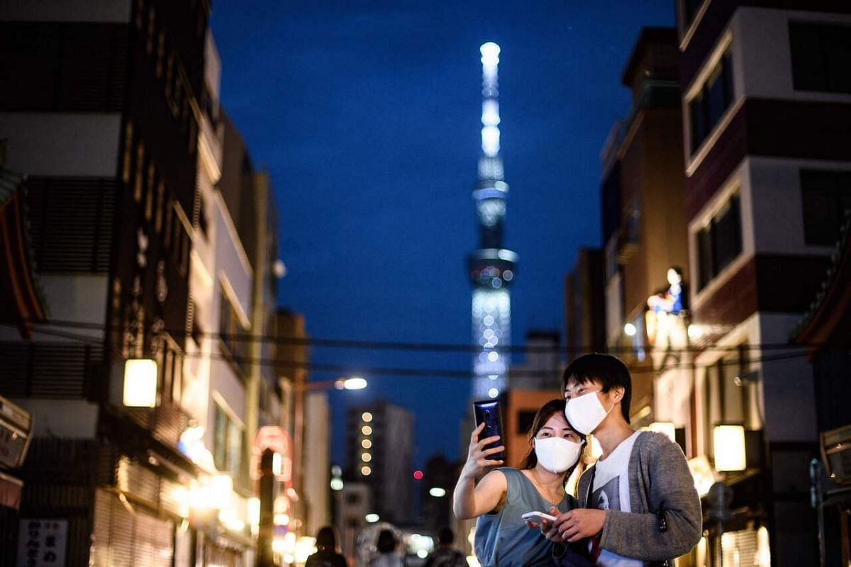 A couple wearing masks takes selfies in front of the Tokyo Skytree on June 28, 2020.