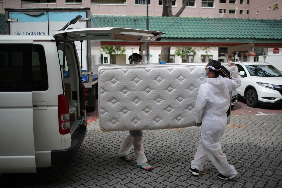 Melvin Chan (left) and Ben Chua transport a donated mattress to a resident.
