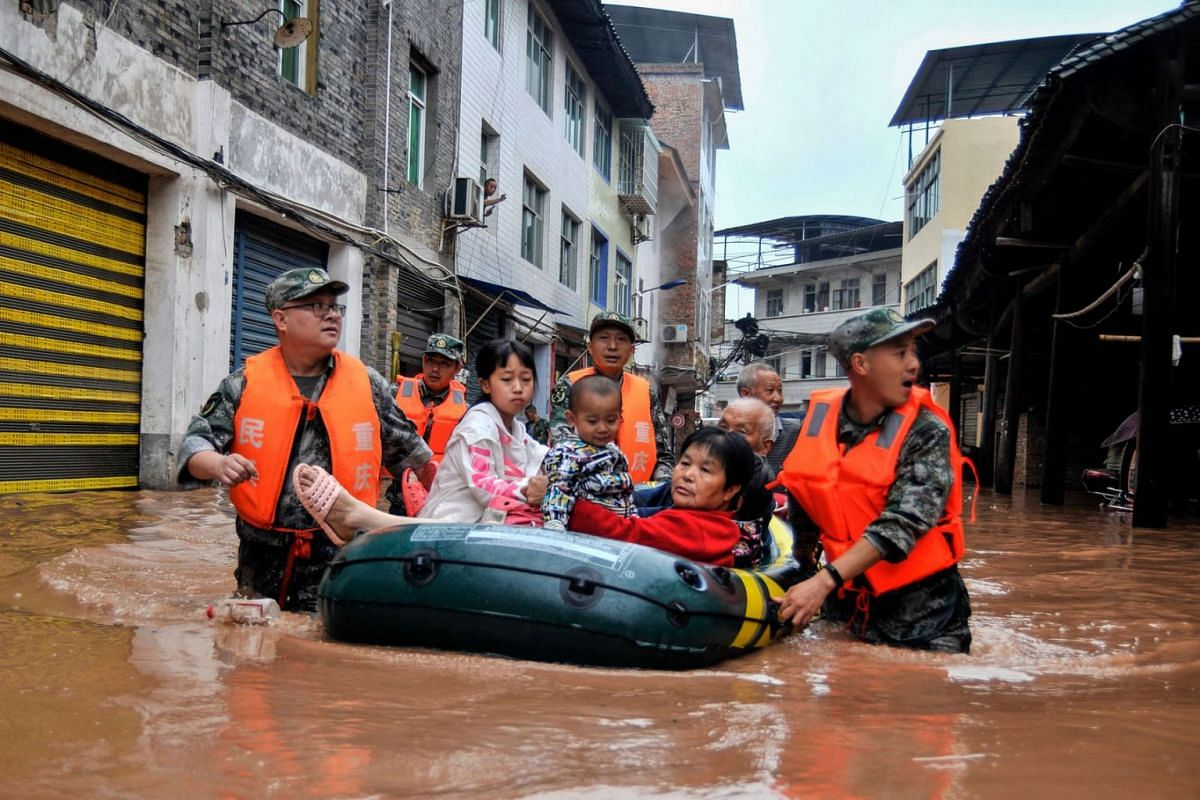 This photo taken on June 28, 2020 shows rescuers evacuating residents in a flooded area after heavy rain in China's southwestern Chongqing. PHOTO:  AFP