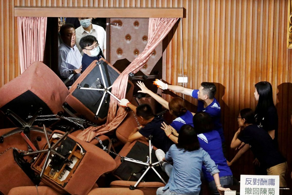Lawmakers from Taiwan's ruling Democratic Progressive Party (DPP) scuffle with lawmakers from the main opposition Kuomintang (KMT) party, who have been occupying the Legislature Yuan, in Taipei, Taiwan, June 29, 2020. PHOTO: REUTERS