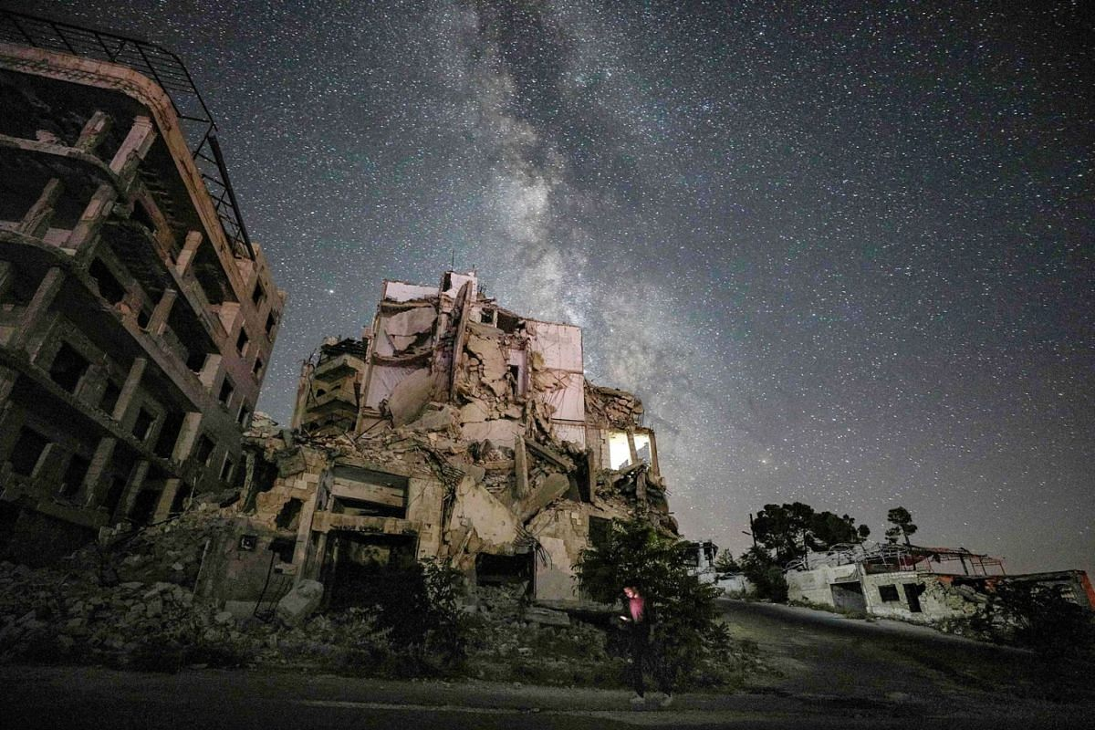 This long-exposure picture taken early on June 27, 2020 shows a man using an cell phone while walking past buildings destroyed by prior bombardment in the town of Ariha in Syria's rebel-held northwestern Idlib province, as the Milky Way galaxy is see