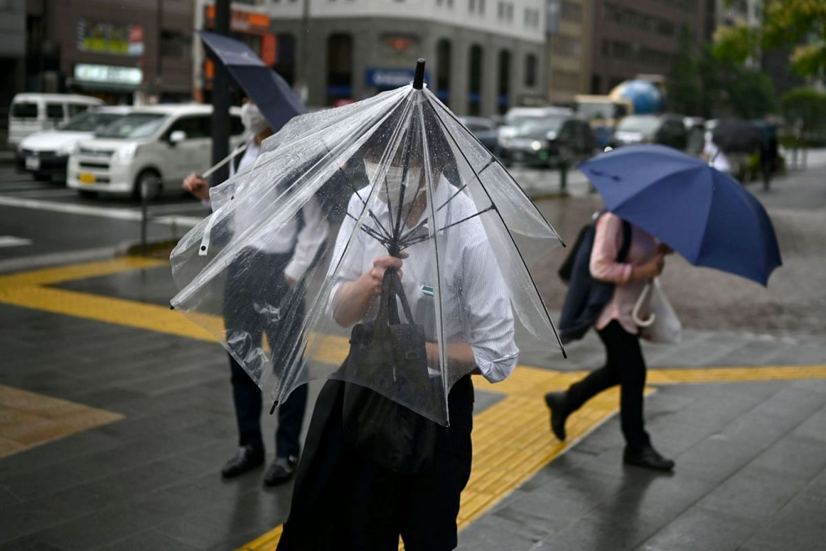 A man tries to shelter under an umbrella as rain and wind from the country's rainy season affects Tokyo on June 30, 2020.  PHOTO: AFP