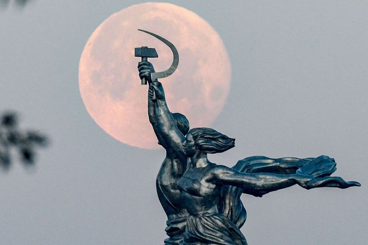 """The full moon is pictured behind the sculpture of """"Worker and Kolkhoz Woman"""" in Moscow on July 6, 2020. PHOTO: AFP"""