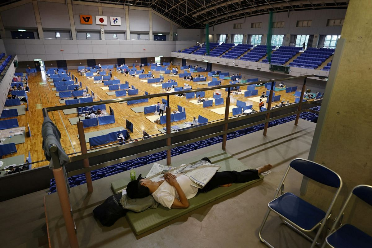 A man lies on a mattress at a shelter for evacuees of torrential rain in Hitoyoshi, Kumamoto prefecture, on July 6, 2020.
